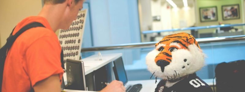 Image of Aubie assisting student at Academic Support desk